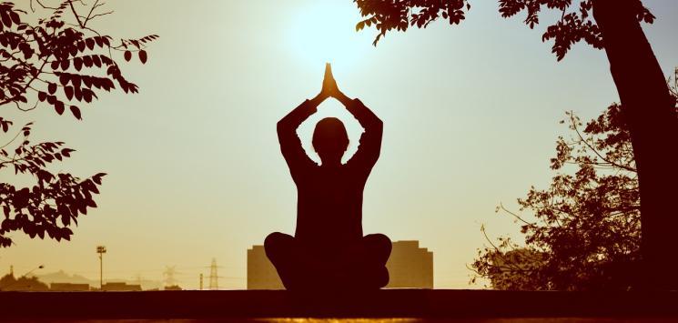 En person mediterer til Qigong ved solnedgang